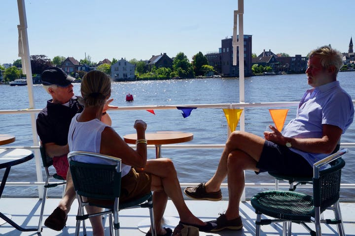 Three people sitting at a table on the boat