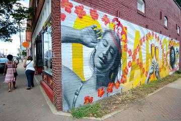 A mural painted on red brick. The mural is a picture of a relaxed woman brushing her hair back with her hand and two Stella Artois glasses clinking.