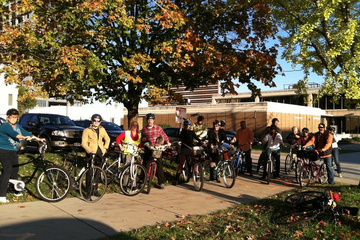 Group of people on bikes with fall foliage behind them on sun on their faces