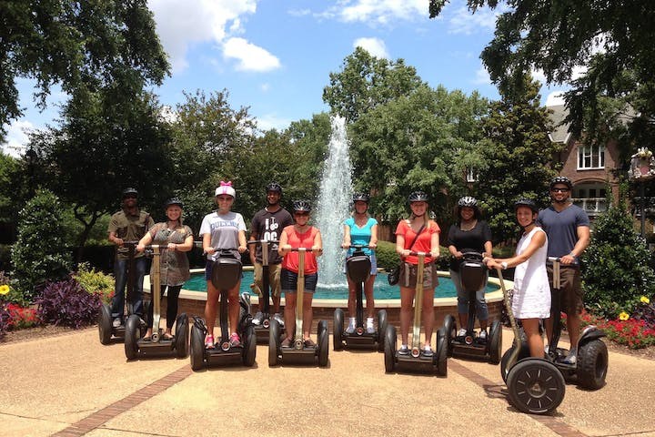 Guests smiling on Segways in front of a beautiful water fountain. Green lush trees are surrounding the water fountain.