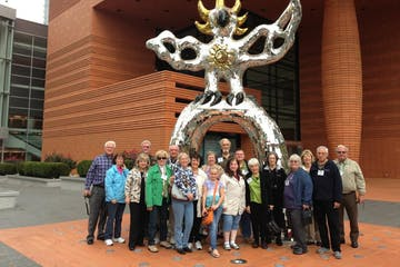 Older guests smiling in front of a giant shiny structure with wings and claws. Structure is gold and silver colors.