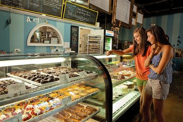 Two ladies eyeing cakes and donuts behind a display glass