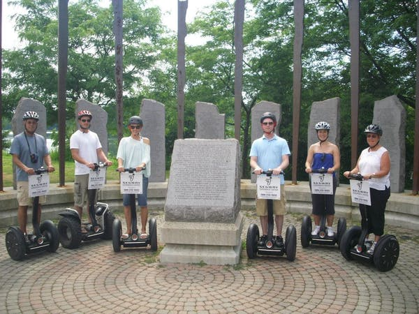 People next to a memorial on a segway