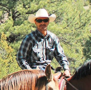 Man with cowboy hat sitting on horse