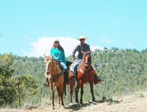 Two horseback riders next to each other on mountain
