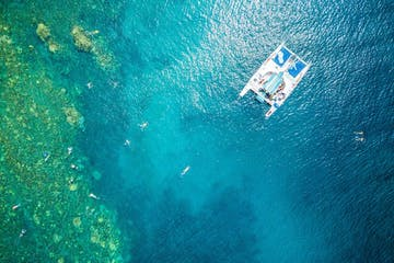 aerial view of a catamaran and swimmers