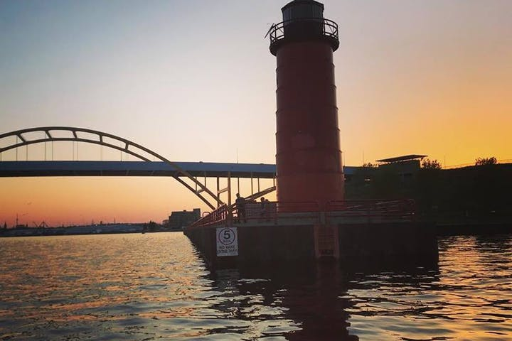 Gold sunset behind a red light house and huge yellow bridge