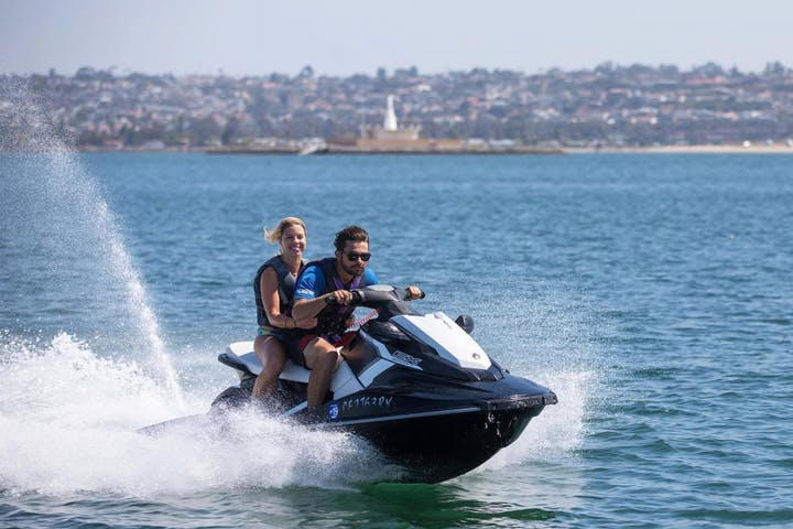 Jetskiers riding through water
