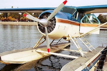 a small airplane sitting on top of a wooden boat in the water