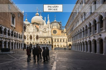 a group of people walking in front of Doge's Palace