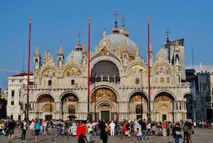 a group of people walking in front of St Mark's Basilica