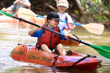 little boy kayaking and smiling with family
