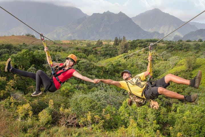 couple ziplining holding hands