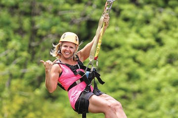 woman ziplining and smiling