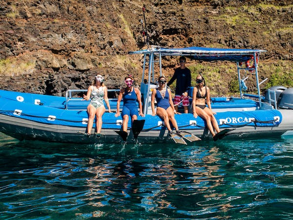 group of snorkelers sitting on side of boat