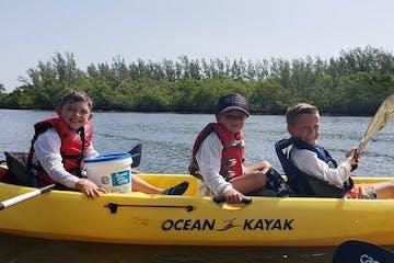 Kids paddling in kayak on water in Jupiter, Florida