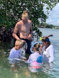 man and kids snorkeling