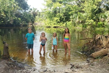 a group of young children standing in a river