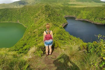 a woman standing on a path in nature and looking at two lakes, one green and one dark lake
