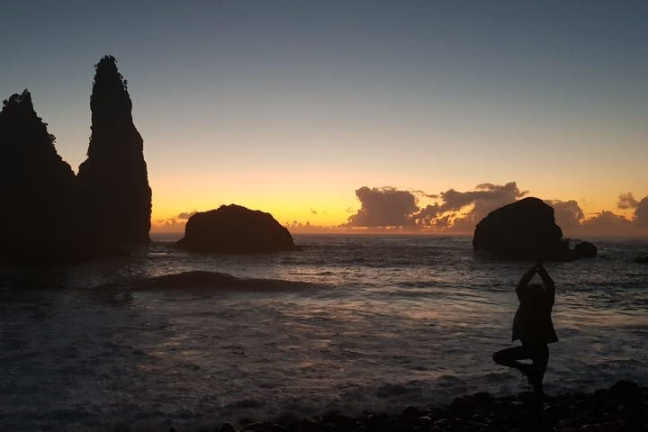A woman in a yoga pose on a beach at sunset watching at the rock formations in the sea
