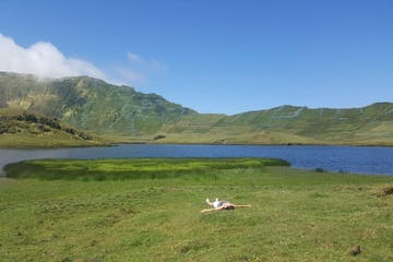 A woman lying in a field next to a big lake