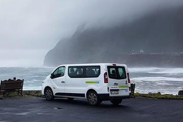 A white van parked next to the sea