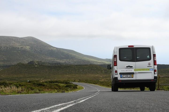 A white van on a road and hills in the background