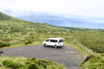 A white van surrounded by green hills
