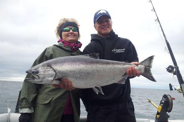 Man and woman holding salmon