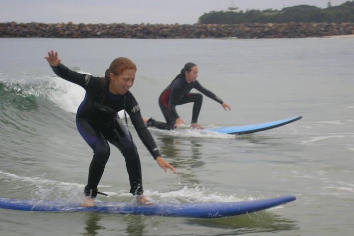 2 young girls doing surfing lessons