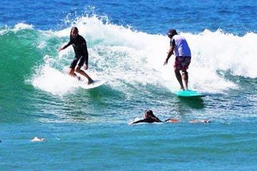 4 teens doing surfing lessons on the beach
