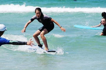 Teenage girl doing surfing lesson with the trainer