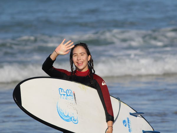 Girl smiling with her surfboard on the beach