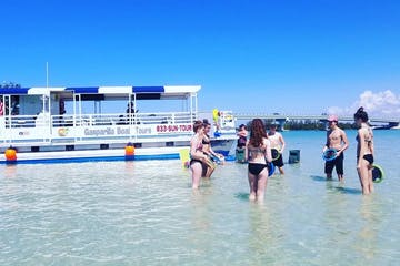 Tourists playing in the water by a boat