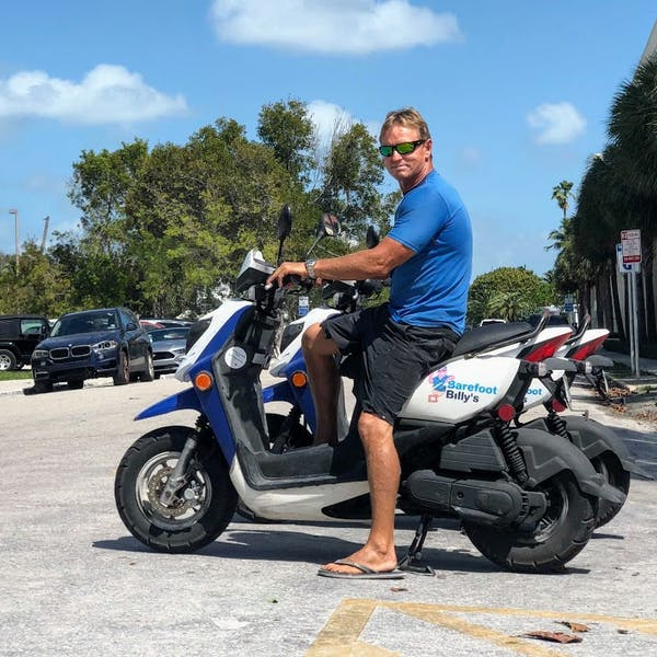 a man sitting on a motorcycle in a parking lot