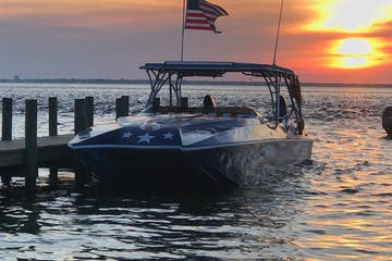 a boat and american flag at sunset