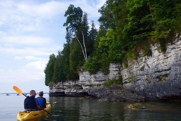 People paddling a kayak toward a bluff on a lake