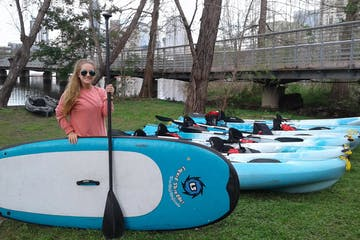 A woman standing near SUPs and kayaks