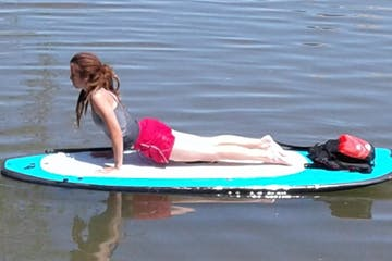 A woman performing yoga on a SUP
