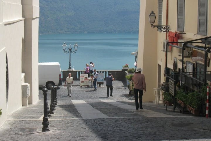 People walking down a cobble street in Italy with views of lake in front