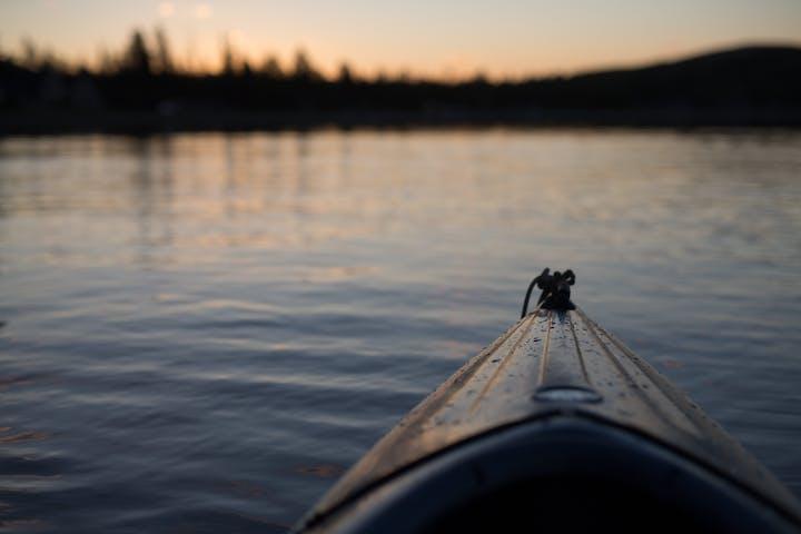 Tip of kayak in sunrise on lake