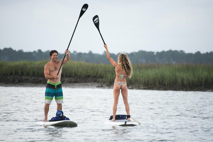 two people high five ing with paddles