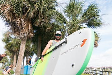 man holding a bishop paddle board
