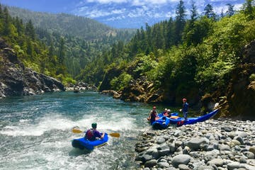Group of kayakers stopped at river bank on white water rapids