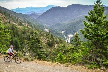 Biker riding along gravel trail alongside mountain cliff