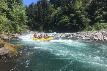 Group of white water rafters navigating down rapids