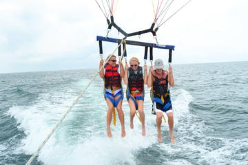 3 parasailers flying low to the water