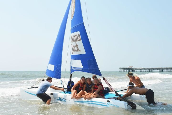 Staff pushing a sailboat off of shore