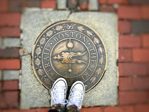 the freedom trail boston plaque on ground with person's shoes