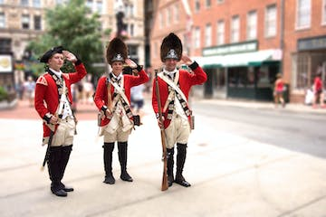 three historically dressed soldiers saluting with guns